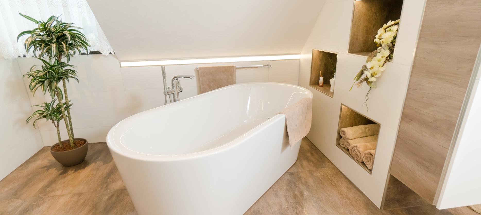 Freistehende Badewanne mit in die Wand integrierten Ablageflächen und Pflanzen