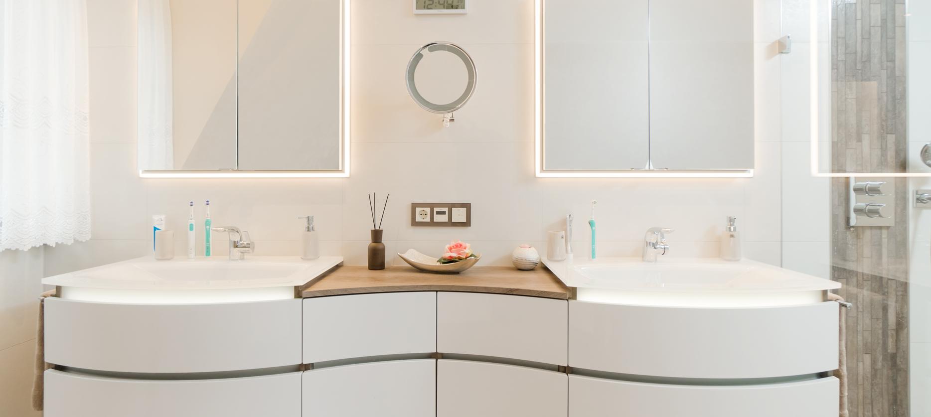 Waschbecken mit stilvollen Unterschränken und Spiegeln mit indirektem Licht