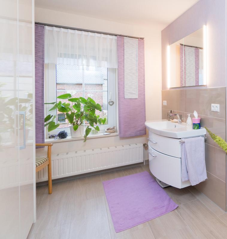 Waschbecken mit indirekt beleuchtetem Spiegel und rosa Dekoration