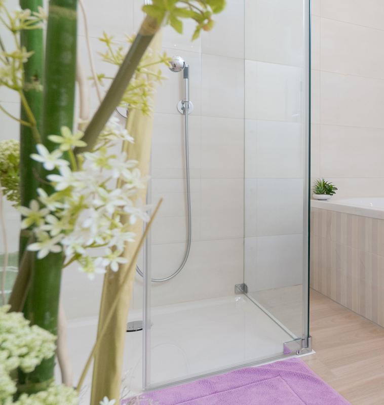 Duschkabine und Badewanne im Einklang mit Pflanzen und rosa Dekoration